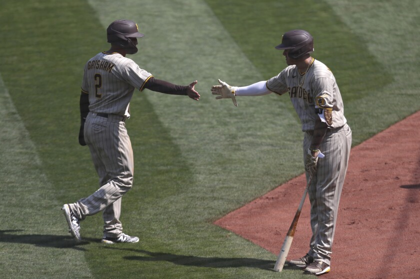 Trent Grisham celebrates with Manny Machado after scoring on a single by Eric Hosmer on Sunday in Oakland.