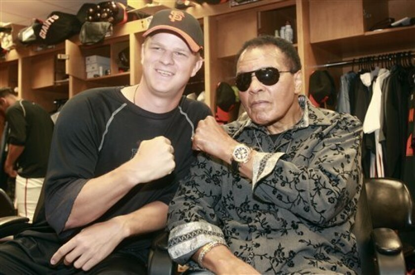 Former boxing champion Muhammad Ali, right, poses for a photograph with San Francisco Giants pitcher Matt Cain in the Giants clubhouse before a spring training baseball game in Scottsdale, Ariz., on Tuesday, March 9, 2010. (AP Photo/Jeff Chiu)