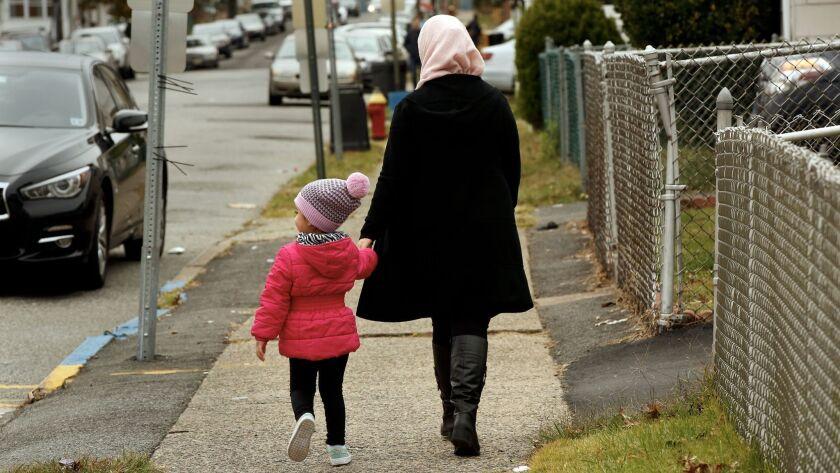 Una mujer camina con su hijo en la calle donde vivía Sayfullo Saipov. Carolyn Cole / Los Angeles Times