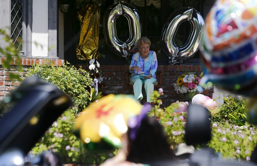 Dancer Joan Bayley marks her 100th birthday by watching a parade from her porch