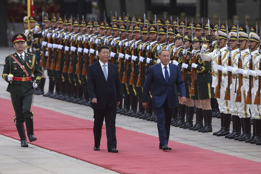 Chinese President Xi Jinping, center, and Kazakhstan President Nursultan Nazarbayev view an honor guard at a welcoming ceremony in Beijing last year.