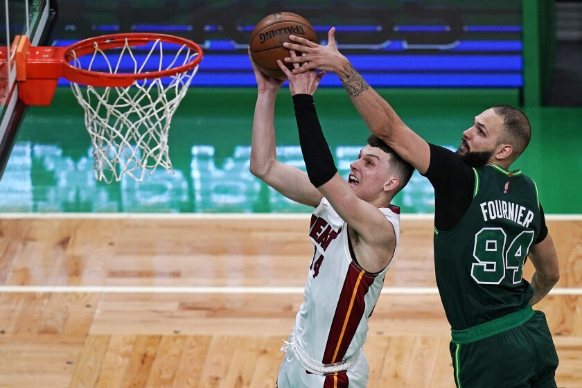 Boston Celtics guard Evan Fournier (94) tries to block a shot by Miami Heat guard Tyler Herro during the second half of an NBA basketball game Tuesday, May 11, 2021, in Boston. (AP Photo/Charles Krupa)