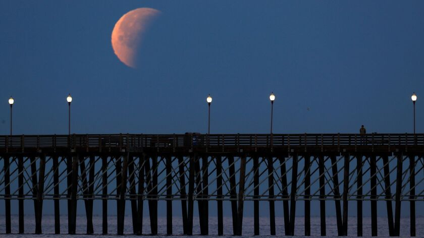 A Blue Moon comes out of a lunar eclipse as it sets past an ocean pier in Oceanside, California