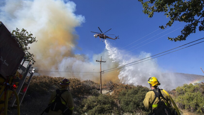 Homes burn, thousands flee as out-of-control brush fire chars more