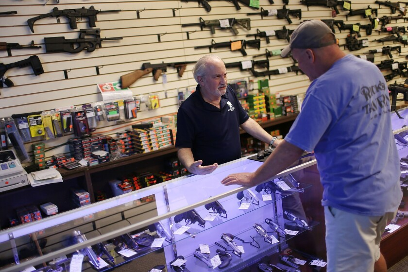 William Gordon, left, helps Mark O'Connor as he shops for a handgun at the K&W Gunworks store in Delray Beach, Fla., on Jan. 5.