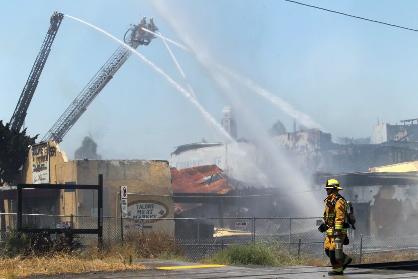 The Talone Meat Market burns in Escondido Thursday as firefighters from multiple agencies work to extinguish the blaze.