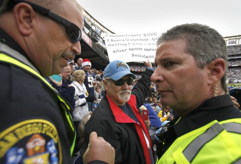 San Diego Police officers flank Brent Mote of Burbank, but originally of San Diego after some fans complained about his sign which is clearly unfavorable to the Chargers and in particular owner Dean Spanos.  After a discussion, he was allowed to keep his sign.  He is a 45-year-ticket holder who sta