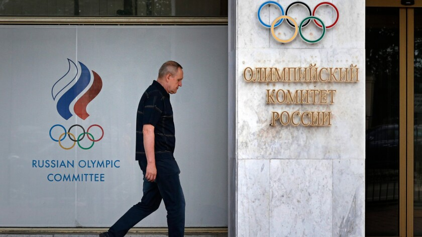 A man walks in front of the Russian Olympic Committee headquarters and Russian Athletics Federation office in Moscow on July 19.