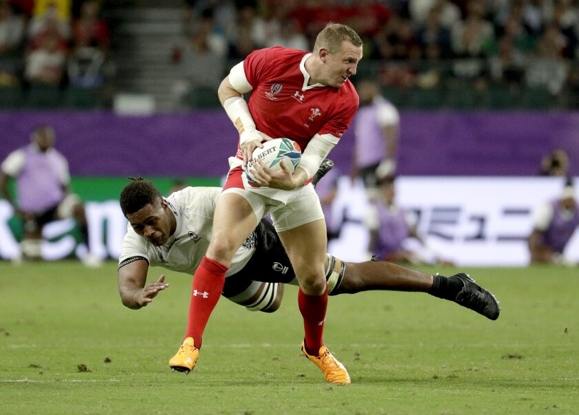 Wales' Hadleigh Parkes makes a run pas a Fijian tackler during the Rugby World Cup Pool D game at Oita Stadium between Wales and Fiji in Oita, Japan, Wednesday, Oct. 9, 2019. (AP Photo/Aaron Favila)