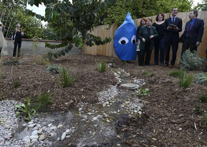 """L.A. County Supervisor Sheila Kuehl, Mayor Eric Garcetti and conservation advocate Andy Lipkis of TreePeople stand with others and watch as water is released electronically from a newly installed 500 liter water cistern into a """"rain garden"""" for replenishing groundwater on Nov. 4."""