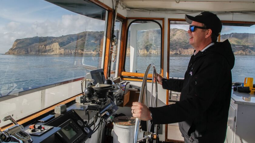 Charles Meyer, captain of the Marietta, navigates the vessel past Point Loma on a recent whale watching tour presented by Birch Aquarium and Flagship Cruises in San Diego, California.