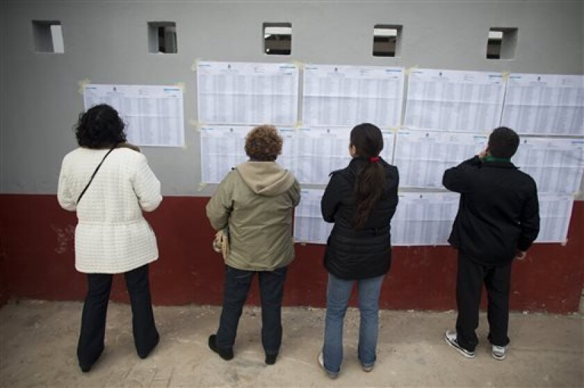 People look for their names in electoral rolls at a polling station in Buenos Aires' Tigre district , Argentina, Sunday, Aug. 11, 2013. Argentines went to the polls in a nationwide mandatory primaries to select candidates for the Oct. 27 midterm election for legislators and senators.(AP Photo/Victor R. Caivano)