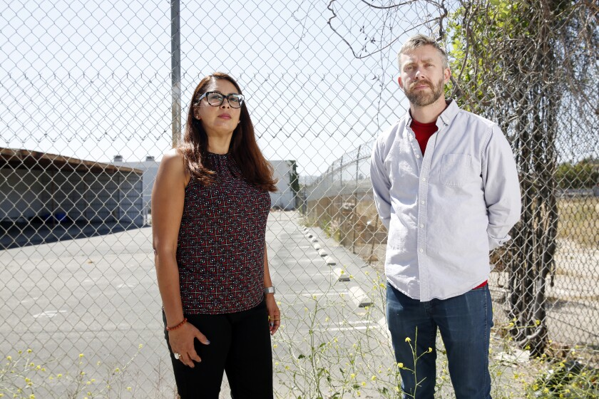Patricia Camacho and Michael Henry Hayden stand in front of a fenced-in parking lot