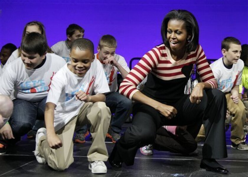 First lady Michelle Obama does the Interlude dance with kids on stage during a Let's Move event with children from Iowa schools, Thursday, Feb. 9, 2012, at the Wells Fargo Arena in De Moines, Iowa, during her three day national tour celebrating the second anniversary of Let's Move. (AP Photo/Carolyn Kaster)