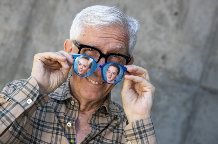 Fritz Coleman with an old pair of his signature large blue glasses with photos of his two boys, Corey and Kelsey.