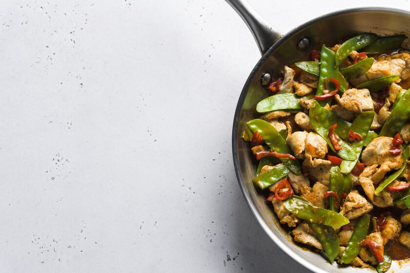 This image released by Milk Street shows a recipe for stir-fried chicken and snow peas. This recipe, with just six ingredients, was inspired by the popular Malaysian dish ayam paprik. (Milk Street via AP)