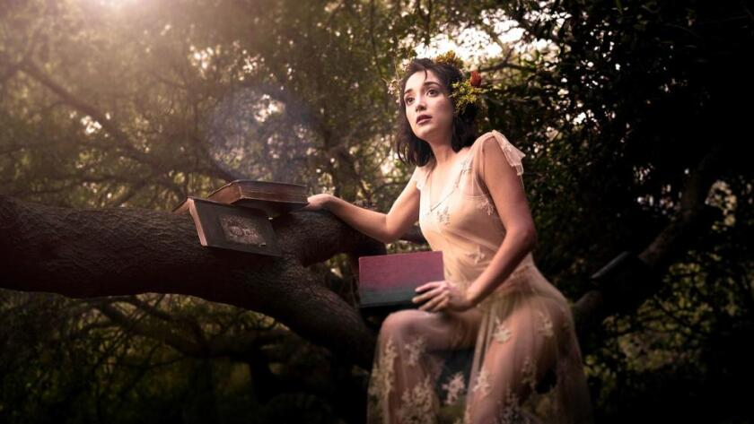 """In a production of """"The Tempest,"""" an actress sits in a tree holding books."""
