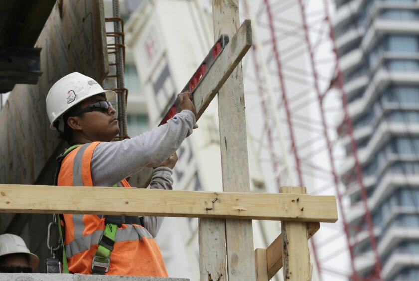 In this Friday, May 16, 2014 photo, a construction worker works on the site of the SoMa at Brickell apartment building in downtown Miami. The Labor Department reports revised figures for productivity in the first quarter on Wednesday, June 4, 2014. (AP Photo/Lynne Sladky)