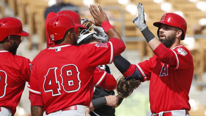 Kaleb Cowart, right, gets high-fives from his Angels teammates after hitting a grand slam against the Chicago White Sox on Monday.