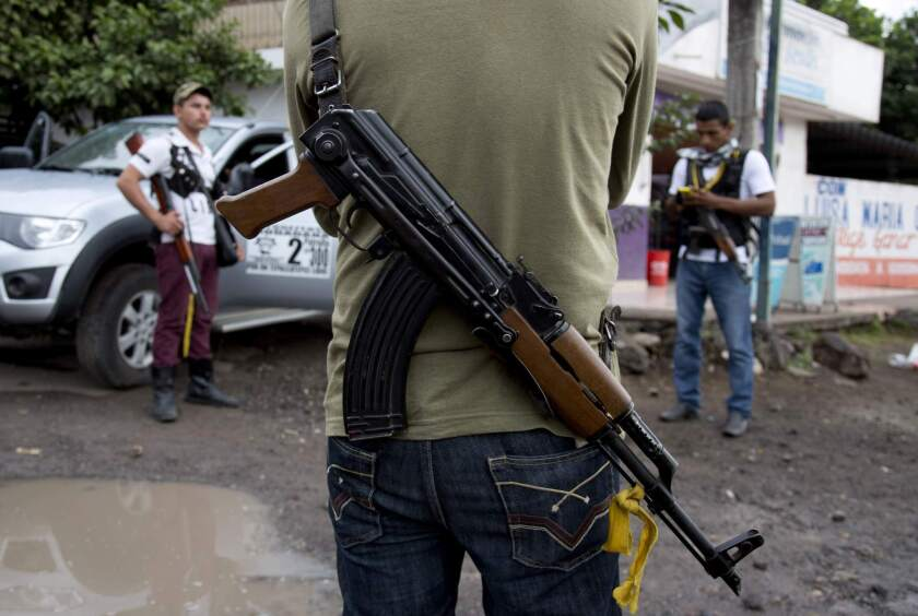 Armed men belonging to the Self-Defense Council of Michoacan stand guard at a checkpoint near the entrance to the town of Antunez, Mexico. The federal government on Tuesday announced billions in aid to the troubled state of Michoacán in the wake of clashes between armed vigilantes and a drug cartel.