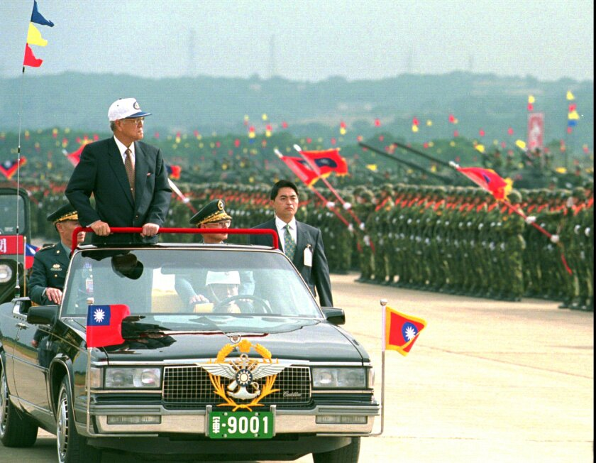 Taiwanese President Lee Teng-hui rides in an open limousine as he inspects armored divisions in 1997.