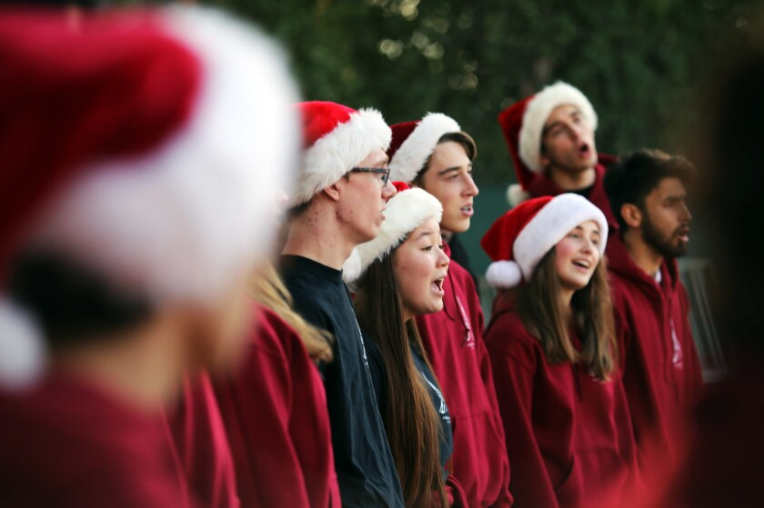 A group of high school singers performs wearing Santa hats.