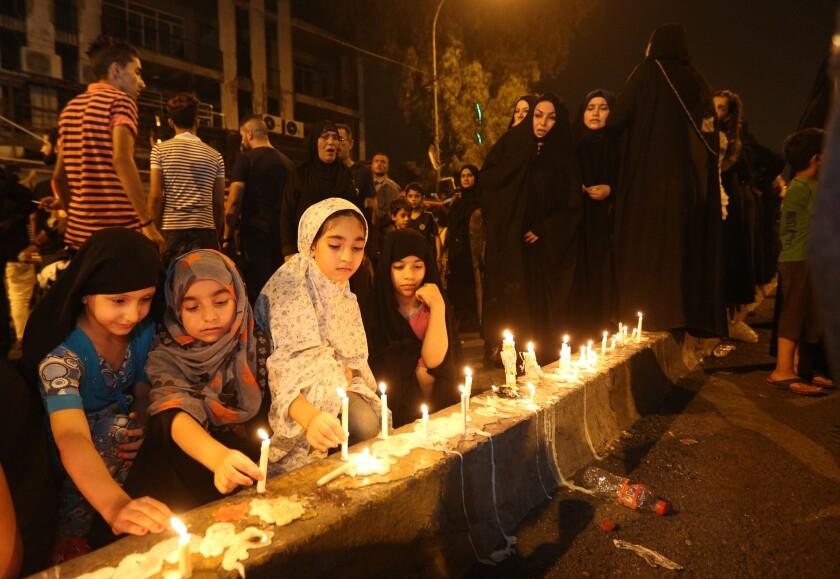Varias personas encienden velas en el lugar de un atentado masivo en Karada, un concurrido distrito comercial donde muchas de las víctimas realizaban compras para el feriado del Eid al-Fitr, en el centro de Bagdad, Irak, el 4 de julio de 2016. (AP Foto/Hadi Mizban)