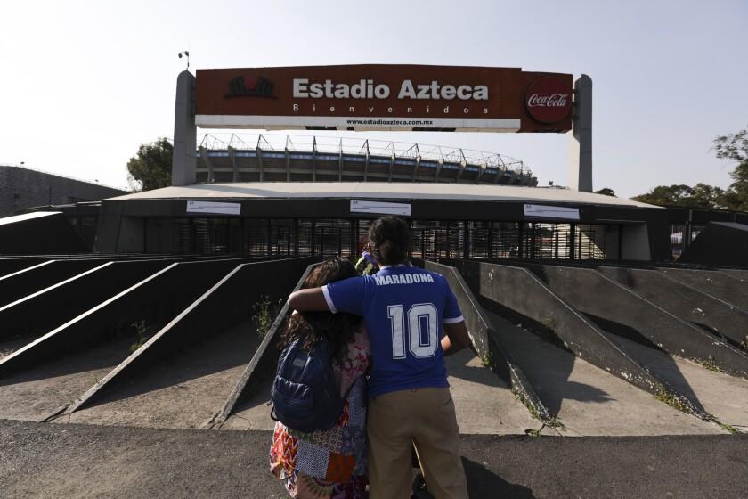 Una pareja, incluido un hombre con una camiseta que lleva el número 10 de Diego Maradona