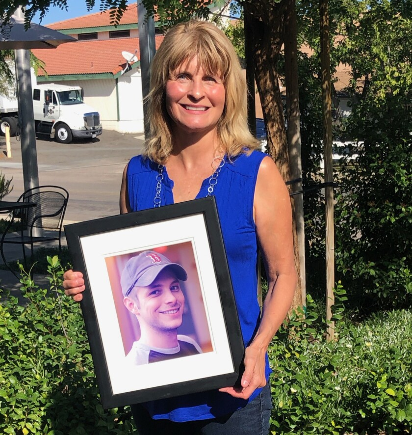 Sy's Fund Executive Director Lorraine Kerz holds a favorite photo of her beloved son, Silas.