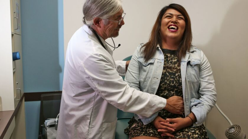 Alexa Vasquez, a transgender female, with physician assistant Lyle Cook at St. John's Well Child & Family Center in South L.A. A new report describes significant health disparities between transgender and gender-majority adults.
