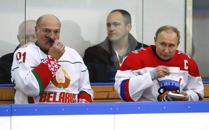 """FILE - In this Friday, Feb. 7, 2020 file photo, Russian President Vladimir Putin, right, and Belarusian President Alexander Lukashenko take a break during a match of the Night Hockey League teams in Rosa Khutor in the Black Sea resort of Sochi, Russia. Lukashenko on Friday, Feb. 14 says Russia insisted on merging the two states during last week's talks on further integrating the countries' economies. He says """"this isn't integration, it's incorporation."""" Tension has been running high between the neighboring ex-Soviet states for several months now. (AP Photo/Alexander Zemlianichenko, file)"""