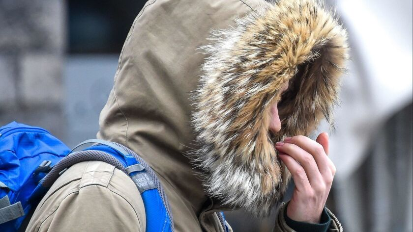 A person shivers during a cold snap in Lille, France. Researchers have found that exercise and exposure to cold prompt the body to release the same fat molecule into the bloodstream.