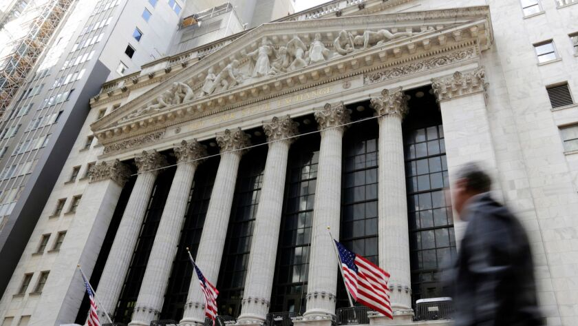 FILE- In this April 5, 2018, file photo, a pedestrian passes the New York Stock Exchange. The U.S. s