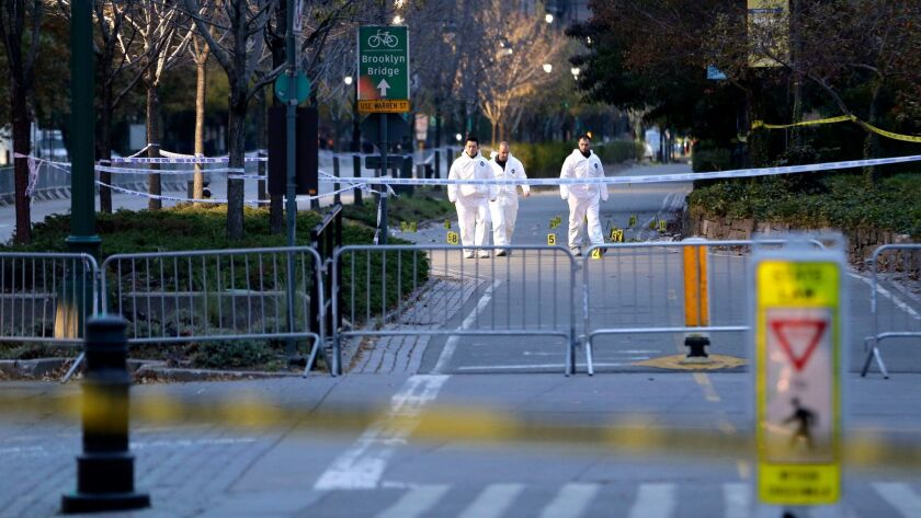Emergency officials walk near evidence markers at the scene where a motorist drove onto a bike path in Lower Manhattan earlier this week, killing eight..