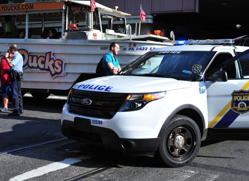 A Philadelphia police officer, left, interviews the husband of a victim who was struck and killed by a Duck Boat near the Philadelphia Convention Center. Police say a Ride the Ducks trolley ran over the woman Friday evening in the Chinatown neighborhood. She was crossing an intersection when police