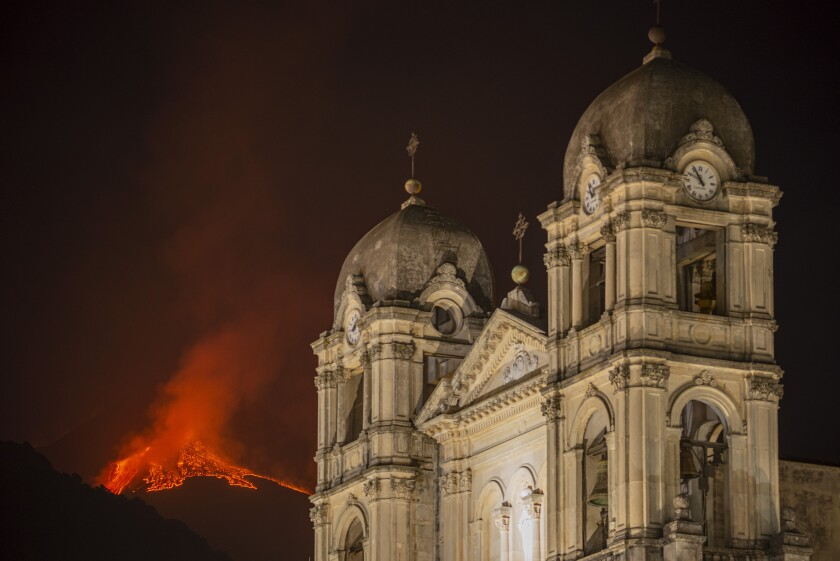 Lava flows from the erupting crater of Mt. Etna, Europe's largest active volcano, framing the church of S. Maria della Provvidenza, in Zafferana Etnea, near Catania, in southern Italian island of Sicily, early Thursday, June 24, 2021. Since Feb. 16, 2021, Mt. Etna has begun a series of spectacular eruptive episodes. (AP Photo/Salvatore Allegra)