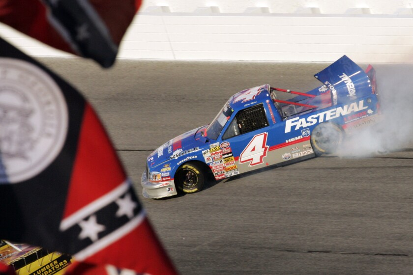 FILE - In this Oct. 28, 2006, file photo, Chase Miller slides his Dodge past an old Georgia flag and a Confederate stars on bars flag during running of a NASCAR Truck series auto race at Atlanta Motor Speedway in Hampton, Ga. NASCAR has a checkered racial history, from a long-time affinity for Confederate flags among the fan base to a driver losing his job just this season for casually uttering a racial epitaph. (AP Photo/Craig Hellman, File)
