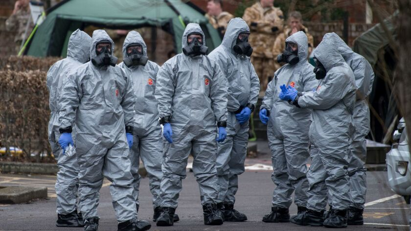 Military personnel wearing protective suits remove a police car and other vehicles from a public car park as they continue investigations into the poisoning of former Russian spy Sergei Skripa in Salisbury, England.