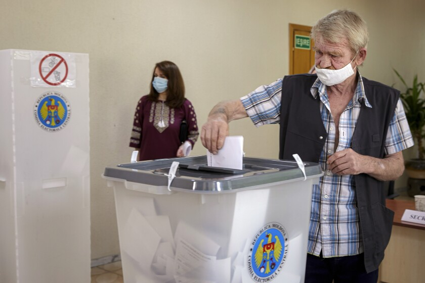 A man casts his vote in a snap parliamentary election, in Chisinau, Moldova, Sunday, July 11, 2021. Moldovan citizens vote in a key snap parliamentary election that could decide whether the former Soviet republic fully embraces pro-Western reform or prolongs a political impasse with strong Russian influence. (AP Photo/Aurel Obreja)