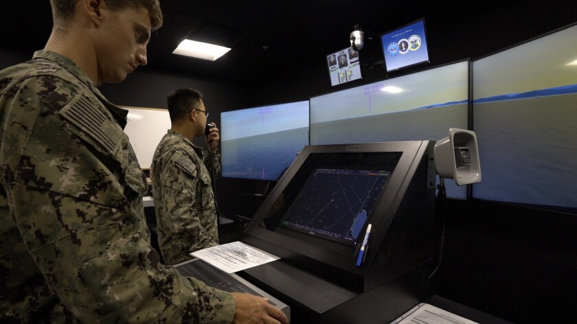 Lt. Davis Chandler and Lt. Daniel Ye stand in front of screens with different images and a water body on them.