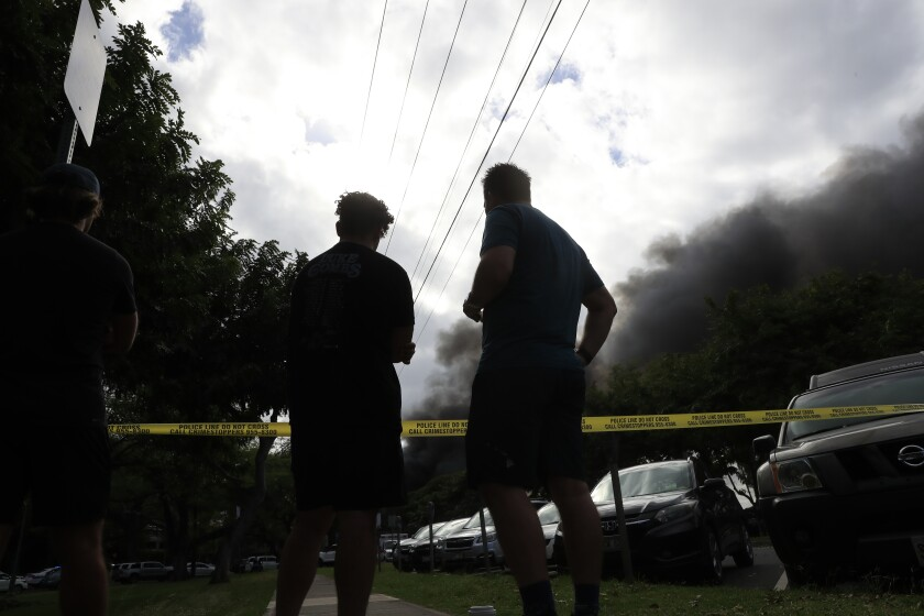 Bystanders watch smoke billow from a house fire after a shooting and domestic incident at a residence on Hibiscus Road near Diamond Head on the island of Oahu.
