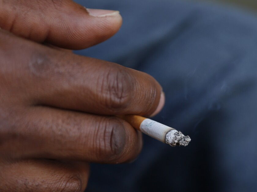 FILE - In this Sept. 17, 2015 file photo, a smoker holds his cigarette outside Oklahoma County Courthouse in Oklahoma City. A federal health panel wants to widen the number of Americans who get yearly scans for lung cancer, by opening the screening to less-heavy smokers. Lung cancer is the nation's top cancer killer, causing more than 135,000 deaths in the U.S. each year. Smoking is the chief cause and quitting is the best protection. (AP Photo/Sue Ogrocki, File)