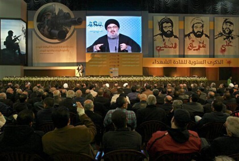 """Hezbollah leader Sheik Hassan Nasrallah speaks via a video link, during a ceremony to mark the anniversary of the death of Hezbollah leaders, in the southern suburbs of Beirut, Lebanon, Saturday, Feb. 16, 2013. Nasrallah has refused to comment on a Bulgarian report that said its members carried out an attack that killed five Israeli tourists in the European nation and he said the """"issue is being followed calmly and carefully."""" (AP Photo/Bilal Hussein)"""