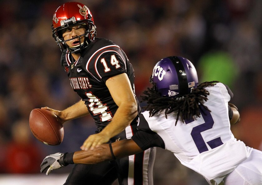 SDSU holder Brian Stahovich tries to get away a pass on a botched field goal as TCU's Jason Verrett approaches in the first quarter on Saturday, Oct. 8, 2011.