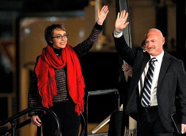 Rep. Gabrielle Giffords and her husband, former astronaut Mark Kelly, wave at the start of a memorial vigil remembering the victims and survivors one year after the Tucson shootings that wounded 13, including Giffords, and killed six.