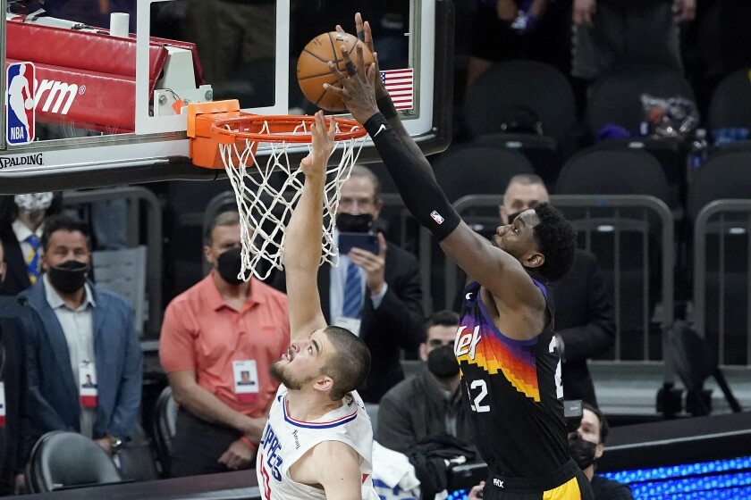 CORRECTS TO SECOND HALF INSTEAD OF FIRST HALF - Phoenix Suns center Deandre Ayton, right, scores over Los Angeles Clippers center Ivica Zubac during the second half of Game 2 of the NBA basketball Western Conference Finals, Tuesday, June 22, 2021, in Phoenix. (AP Photo/Matt York)
