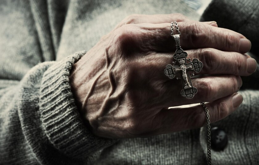 Elderly hands with rosary