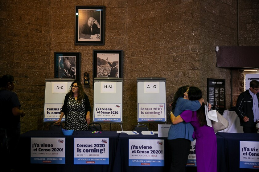 People hug and talk in front of a table festooned with Census 2020 posters at a 2019 workshop