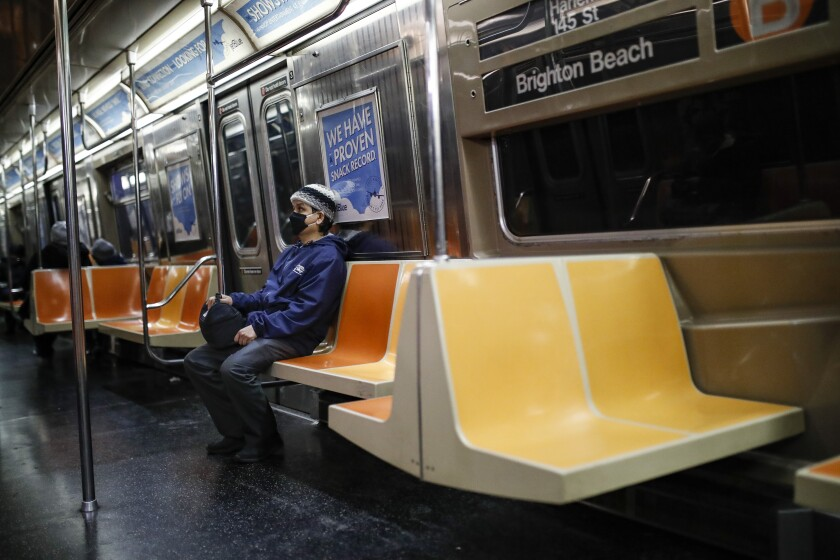 A commuter wears a face mask while riding the a nearly empty subway car into Brooklyn, Thursday, March 12, 2020, in New York. New York City Mayor Bill de Blasio said Thursday he will announce new restrictions on gatherings to halt the spread of the new coronavirus in the coming days, but he hopes to avoid closing all public events such as Broadway shows. For most people, the new coronavirus causes only mild or moderate symptoms. For some it can cause more severe illness. (AP Photo/John Minchillo)