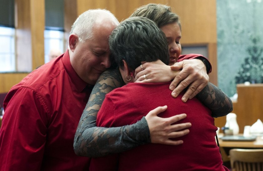 Thom DeWolf, left, hugs his daughter Rachel, center, and wife, Kris, at the Washtenaw County Trial Court, Tuesday, Jan. 27, 2015, in Ann Arbor, Mich. Joei Jordan was convicted for his role in the death of Paul DeWolf, a University of Michigan medical student who was shot during a 2013 armed robbery
